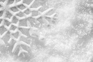 A low-contrast image of a snowflake on snow.